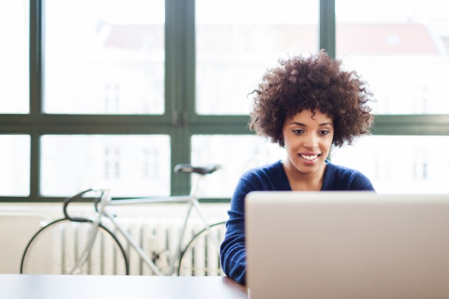 Young black woman working in a modern loft space behind a laptop.